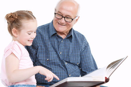 grandfathers: Portrait of a grandfather wearing blue checkered shirt looking at his small pretty granddaughter sitting next to him pointing into the big brown book and smiling, isolated on a white background Stock Photo