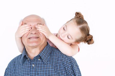 白地に青格子縞を身に着けている祖父と目を閉じて保持している彼の後ろに立っている彼の小さな可愛い孫娘の肖像画推測ゲームは、人を再生分離