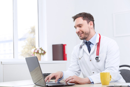 the cardiologist: Good news. Pleasant cardiologist searching through the Internet and smiling while sitting at the table.