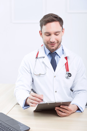 upbeat: Upbeat mood. Smiling cardiologist filling papers and preparing to check patients while sitting at the table Stock Photo