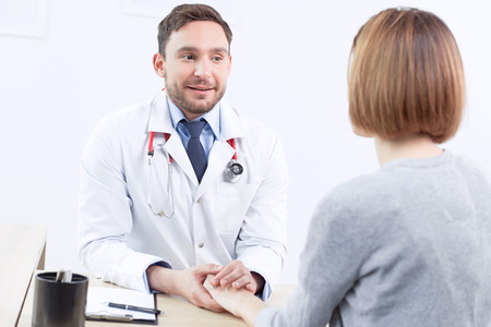 the cardiologist: Everything will be OK. Pleasant cardiologist talking to the patient and smiling while holding his hand on table. Stock Photo