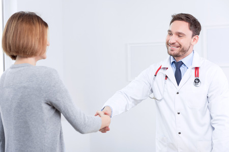 good bye: Good bye. Smiling professional doctor shaking hands with the patient and looking at her while leaving. Stock Photo