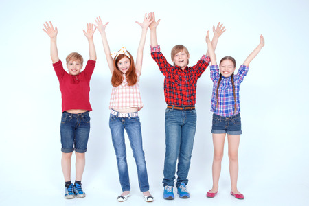 overwhelming: Overwhelming joy. Vivacious children smiling and putting their hands in the air while standing together isolated on white background.