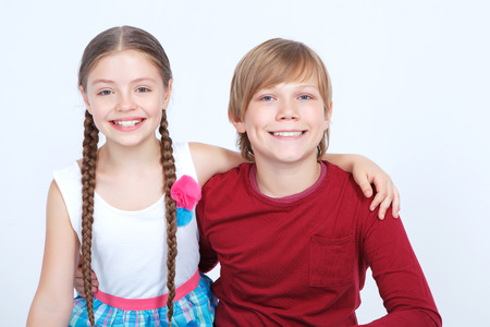 girl bonding: Childish love. Smiling boy and girl bonding to each other while sitting on the white background