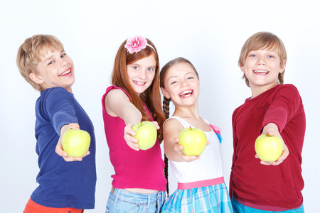 upbeat: Taste it. Little upbeat friends standing together and holding fresh apples while smiling.