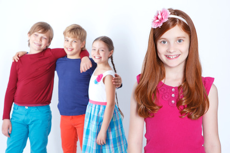 agreeable: We are friends. Red-haired agreeable girl smiling with three friends bonding to each other on the background.