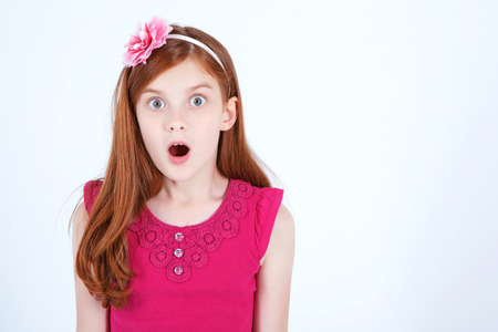 Wow. Pretty young girl holding her hands straight and opening the mouth while expressing surprise. Stock Photo