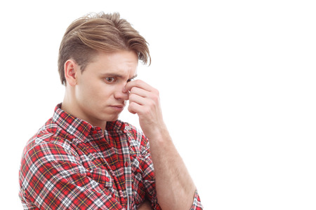 eyes open: Feeling hopeless. Distempered guy touching his nose and keeping eyes open while standing  isolated on white background.
