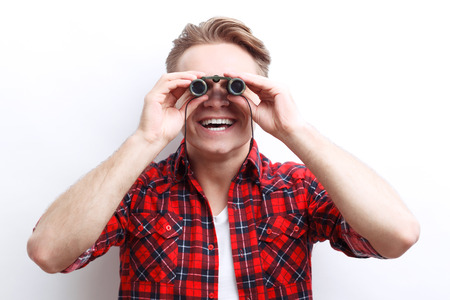 laugher: I see you. Nice guy holding the binoculars in his hands and looking through it while standing isolated on white background.