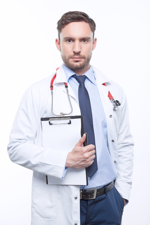 seriousness: Overwhelming seriousness. Serious doctor holding  papers and keeping the hand in his pocket while standing isolated on white background Stock Photo