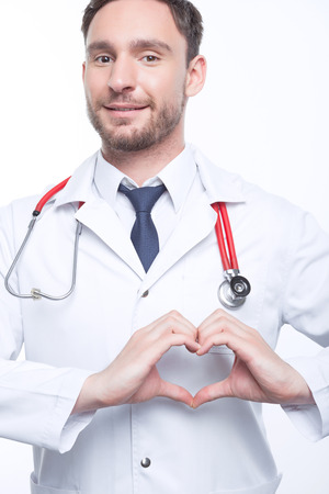 hand care: Beating heart. Pleasant young doctor keeping his hand together and showing care. Stock Photo