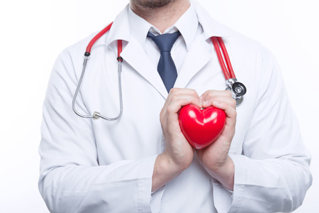 the cardiologist: Feal the beat. Young cardiologist holding the heart in his hands with care while standing on white background.