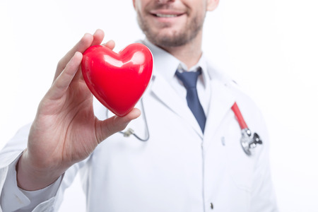 the cardiologist: Take care of your health. Young smiling cardiologist holding the heart in his right hand  while standing isolated on white background.