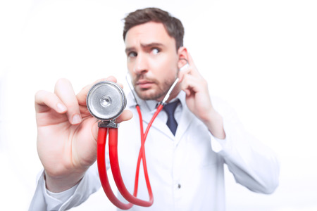 the cardiologist: Busy at work. Close up of stethoscope with young bearded thoughtful  cardiologist standing  on the white background.