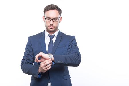 llegar tarde: No llegues tarde. Barbudo hombre de negocios joven que toca su reloj de pulsera y mantener la mirada hacia abajo mientras piensa. Foto de archivo