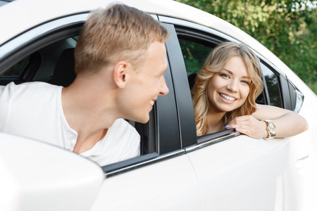 man looking out: Happy journey. Portrait of a handsome young man looking out of the window of the car on his beautiful blond girlfriend with curvy hair sitting in the back seat smiling