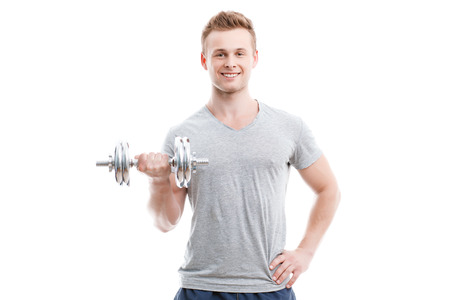 Waist up portrait of a young handsome man wearing grey t-shirt standing smiling and holding a silver dumbbell in his hand showing his muscled biceps during training, isolated on white background