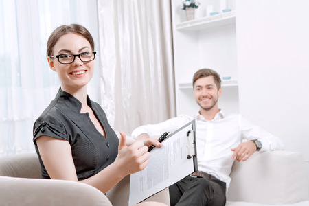 health professionals: Portrait of a beautiful woman psychologist wearing glasses and black blouse sitting at the light doctor office smiling holding some documents, her patient sitting on the background wearing a suit