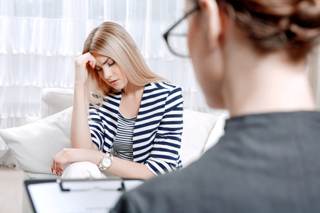 mental problems: Young blond woman sitting on a couch holding her head sadly crossed telling about her problems, doctor with clipboard listening to them and making notes during therapy session, selective focus Stock Photo