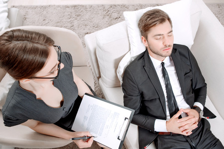 career counseling: Top view of a psychologist sitting in the armchair holding a clipboard in her hands and looking at her client lying on a couch near relaxing ,thinking of his problems during therapy session
