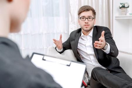 Jonge man draagt een zwart pak zittend op een bank vertelt zijn problemen en gesticuleren, psycholoog met klembord naar hem te luisteren en het maken van aantekeningen tijdens de therapie sessie, selectieve aandacht