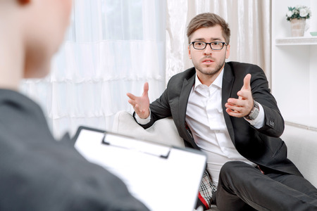 selective focus: Young man wearing a black suit sitting on a couch telling his problems and gesticulating, psychologist with clipboard listening to him and making notes during therapy session, selective focus Stock Photo