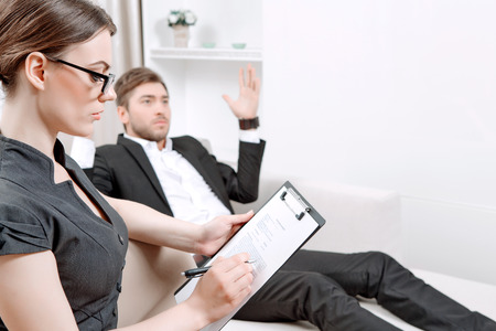 counseling session: Young man wearing a black suit lying on a couch telling his problems and gesticulating, psychologist with clipboard listening to him and making notes during therapy session, selective focus