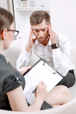 career counseling: Young man wearing a white shirt sitting on a couch and holding hands near head thinking of his problems, psychologist with clipboard talking to him making notes during therapy session, selective focus Stock Photo