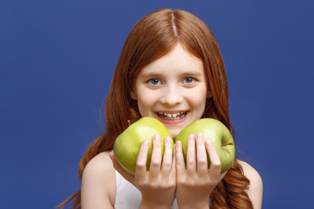 Favorite fruit. Nice little red-haired girl holding hands ahead and keeping apples in them while smiling.