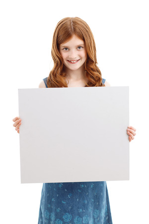 laugher: Happy childhood. Little upbeat girl holding white board with two hands while standing isolated on white background.