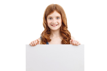 redhaired: Overwhelming joy. Cute red-haired little girl holding white card with two hands and smiling while standing isolated on white background.
