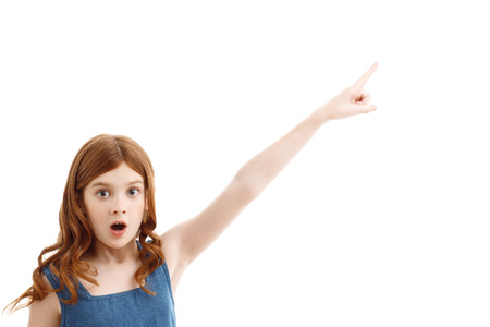 upbeat: Hey. Upbeat red-haired little girl holding his hand up and screaming while expressing  surprise Stock Photo