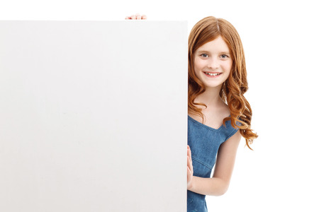 vivacious: Happy childhood. Vivacious nice little girl standing near white box and touching it while smiling.