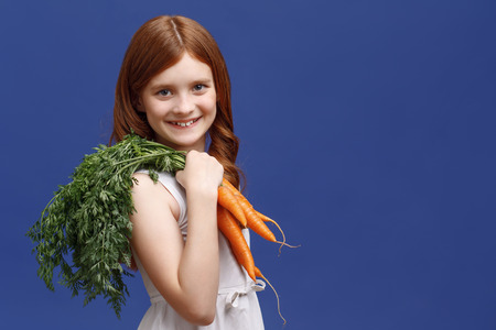 vivacious: Be healthy. Vivacious red-haired little girl holding the bunch of carrot on her shoulder and smiling while standing half-turned.