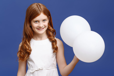 laugher: It is party time. Vivacious little girl holding balloons with one hand and smiling while standing isolated on blue background.