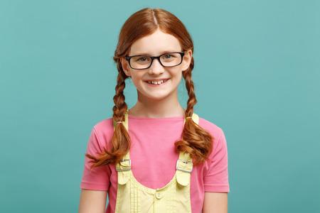 diligente: Chica diligente. Ni�a bastante inteligente con gafas y mirando hacia el futuro, mientras que de pie aislado en fondo azul.
