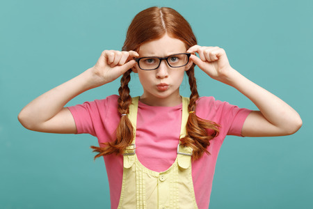 laugher: Involved in studying . Pleasant little girl wearing glasses and holding them while standing on white background.