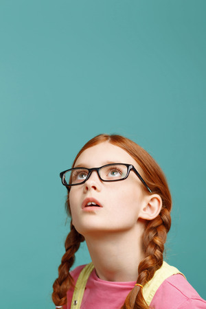 consuming: Consuming interest. Nice little red-haired girl holding the head and looking up while feeling interested.