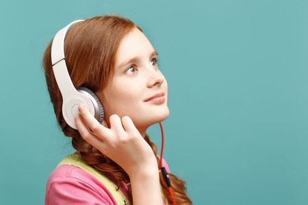laugher: Feeling delighted. Nice little red-haired girl touching her headphones and looking up while standing half-turned isolated on blue background. Stock Photo