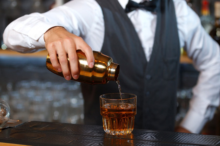 Close up photo of a bartender holding a golden shaker in his hand and pouring a cocktail in a low wide glass, shelves full of bottles with alcohol on the background
