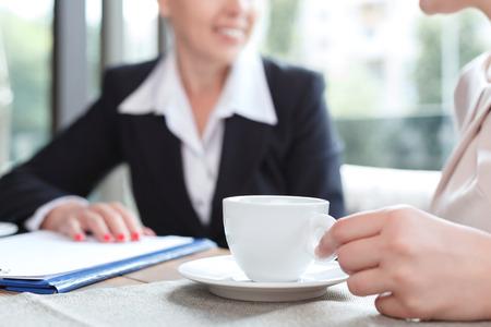 비즈니스 점심 식사 시간 동안 레스토랑에서 커피와 그녀의 비즈니스 파트너의 컵을 들고 여자의 손의 사진을 닫습니다, 선택적 포커스 스톡 콘텐츠