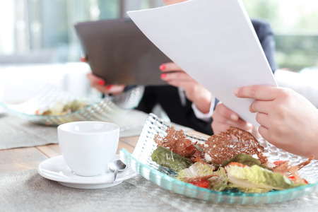 lunch table: Close up photo of hands on a woman holding some papers and her colleague with a tablet, green salad and a cup of coffee on the table, in a restaurant during business lunch selective focus Stock Photo