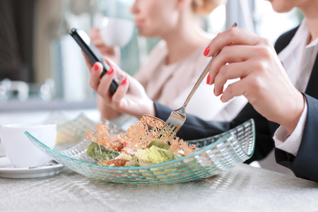 Close up photo of hands on a woman holding a fork eating a salad and a mobile phone reading some important emails, in a restaurant during business lunch selective focus Stock Photo