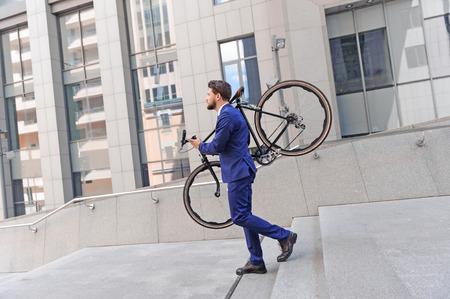 bajando escaleras: Empresario vivaz celebración de su bicicleta en sus hombros y mirando directamente al bajar escaleras.