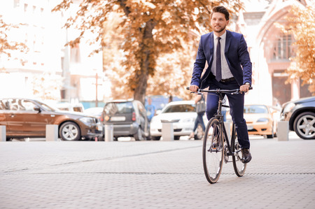 modern lifestyle: Pleasant bearded businessman smiling and looking up while riding bicycle