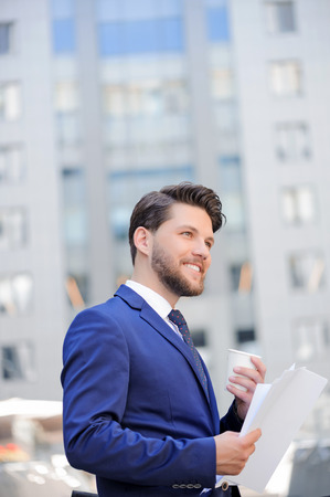vivacious: Vivacious nice bearded businessman smiling and holding papers while drinking coffee. Stock Photo
