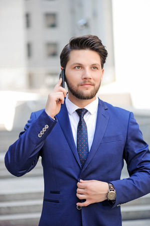 waist up: Waist up of pleasant handsome bearded businessman holding mobile phone near ear and looking up while talking.