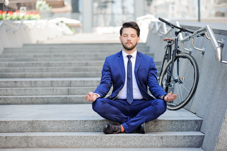 business suit: Pleasant bearded young businessman keeping his eyes closed and sitting on the stairs while practicing yoga.