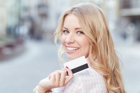 Portrait of a beautiful blond girl with long wavy hair wearing pink dress, standing back to us and turning looking at us holding a credit card