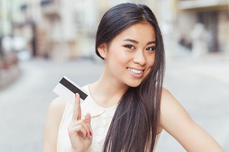 긴 머리를 가진 아름 다운 아시아 여자의 초상화, 베이지 색 블라우스를 입고 미소와 그녀의 손에 신용 카드를 들고
